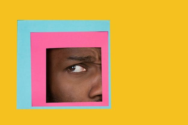 Oko afrykańskiego mężczyzny zerkające przez kwadrat na żółtym tle