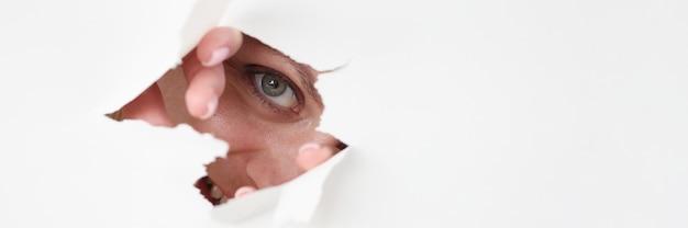 Oko kobiety wygląda przez dziurę w białym papierze