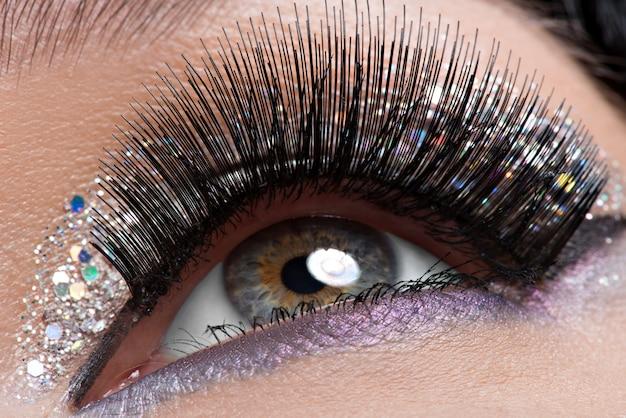 Oko kobiety z długimi czarnymi sztucznymi rzęsami i kreatywnym, modnym, jasnym makijażem