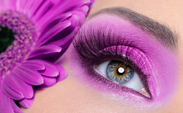 Oko kobiety z fioletowym makijażem i długimi sztucznymi rzęsami - kwiat gerber