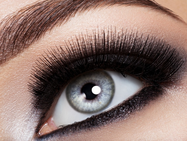 Oko kobiety z makijażem podbitego oka. obraz w stylu makro. długie rzęsy