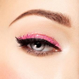 Oko kobiety z różowym makijażem oczu. obraz w stylu makro