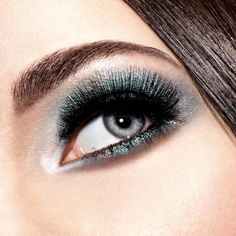 Oko kobiety z turkusowym makijażem. długie sztuczne rzęsy. makro