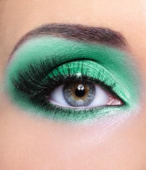 Oko kobiety z zielonymi cieniami do powiek - makijaż moda