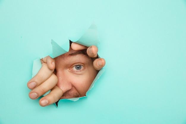 Oko patrzą przez dziurę w papierze. człowiek patrząc przez otwór w niebieskim papierze.