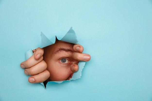 Oko patrzą przez dziurę w papierze.