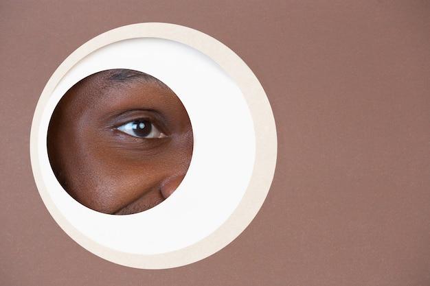 Oko uśmiechniętego afroamerykańskiego mężczyzny zerkającego przez koło na brązowym tle