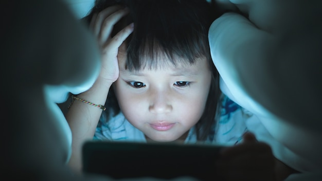 Oko z bliska mała dziewczynka ogląda wideo w tablecie na łóżku, w nocy błyski światła odbijające się od ekranu
