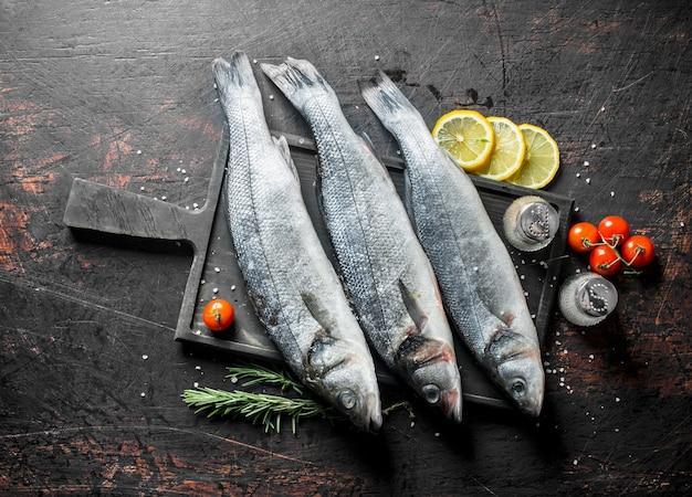 Okoń morski z surowej ryby z cytryną, rozmarynem i przyprawami. na ciemnym tle rustykalnym