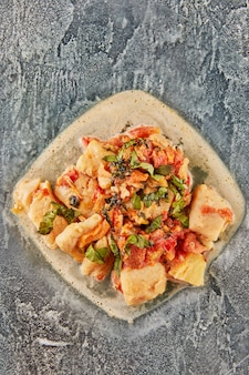 Okoń rybny z pomidorami kopru włoskiego i bazylią w sosie na szklanym talerzu. płaskie ułożenie