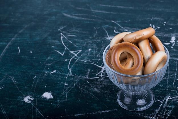 Okrąg ciasteczka w szklanej filiżance na niebieskim tle, kąt widzenia.