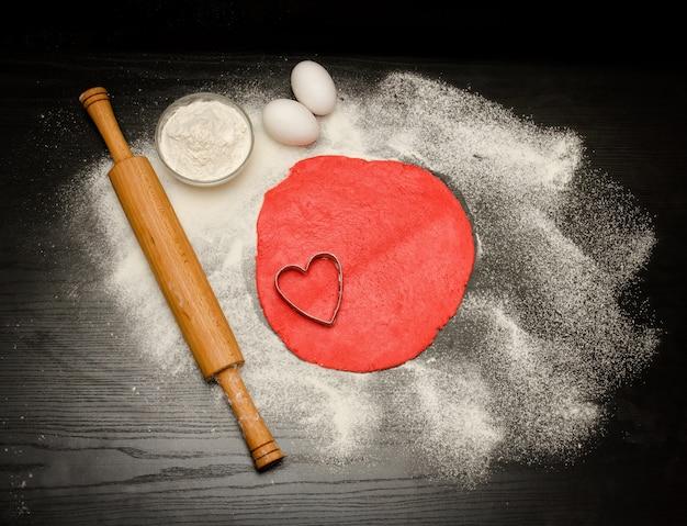 Okrąg czerwonego ciasta z wycięciem w kształcie serca. czarny stół posypany mąką, wałkiem i jajkami. widok z góry