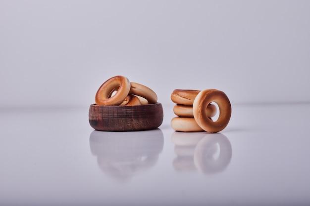 Okrąg krakersy lub bułeczki z ciasta w drewnianym kubku odizolowane na środku.