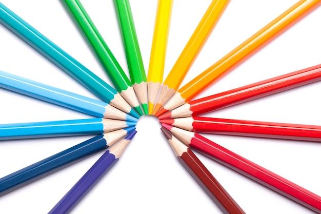 Okrąg lub półkole kolorowych ostrych ołówków wylewa się w środku na białym tle odizolowane.