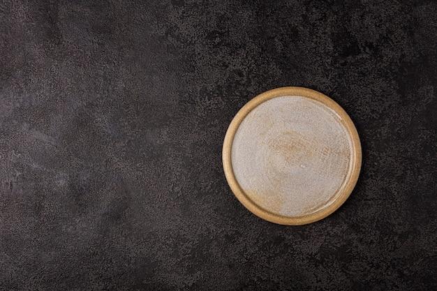 Okrągła beżowa płyta ceramiczna na ciemnym tle strukturalnym widok z góry copyspace