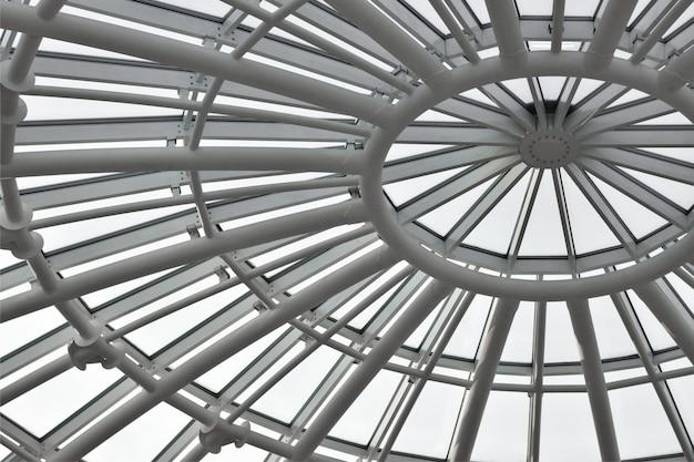 Okrągła biała metalowa rama szklanego dachu budynku, widok z dołu