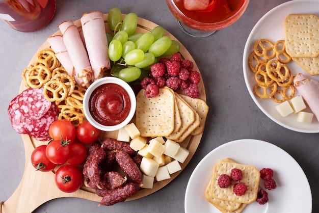 Okrągła deska do wędlin z kiełbasą, serem, krakersami i owocami, talerze z przystawką, zbliżenie.