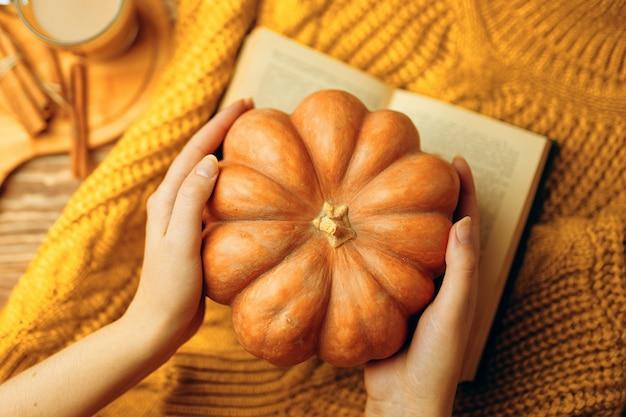 Okrągła dojrzała dynia w dłoniach gorąca latte otwórz romantyczną książkę i ciepły sweterek z dzianiny jesienna kompozycja...