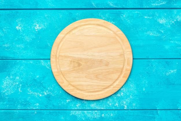 Okrągła drewniana deska do krojenia do pizzy na niebieskim drewnianym stole. makieta do projektu żywności. widok z góry.