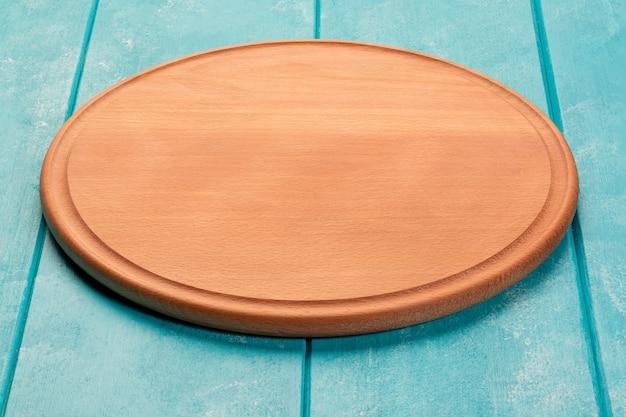 Okrągła drewniana deska do krojenia do pizzy na niebieskim drewnianym stole. pełna głębia ostrości. makieta do projektu żywności.