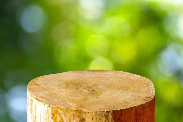 Okrągła drewniana piła wyciąć kształt cylindra do wyświetlania produktu z zielonym abstrakcyjnym tłem bokeh