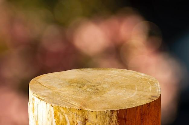 Okrągła drewniana piła wycinana w kształcie cylindra do wyświetlania produktu z różowym abstrakcyjnym tłem bokeh
