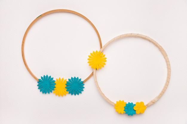 Okrągła drewniana rama ozdobiona żółtymi i niebieskimi kwiatami na białym tle