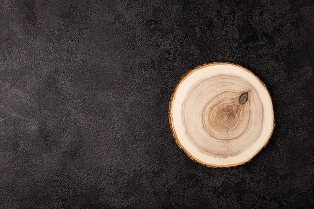Okrągła drewniana taca na ciemnym tle strukturalnym, widok z góry
