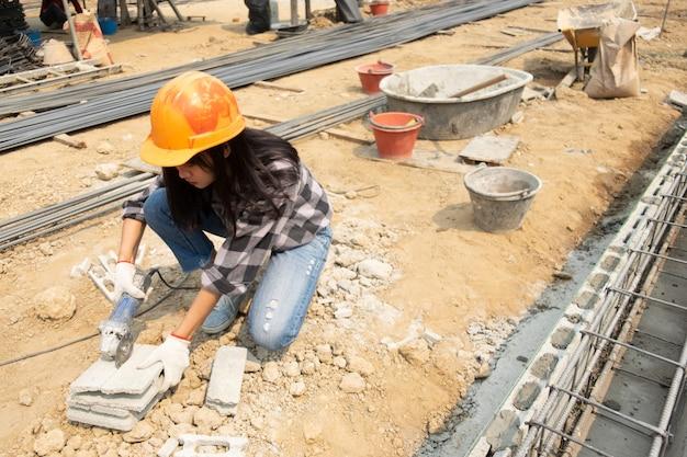 Okrągła piła w rękach konstruktora, praca przy układaniu płyt chodnikowych.