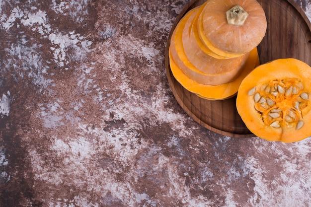 Okrągła pokrojona dynia na drewnianym talerzu w górnym rogu