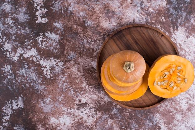 Okrągła pokrojona dynia w drewnianym talerzu, widok z góry