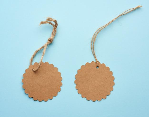 Okrągła pusta etykieta z brązowego papieru przewiązana sznurkiem