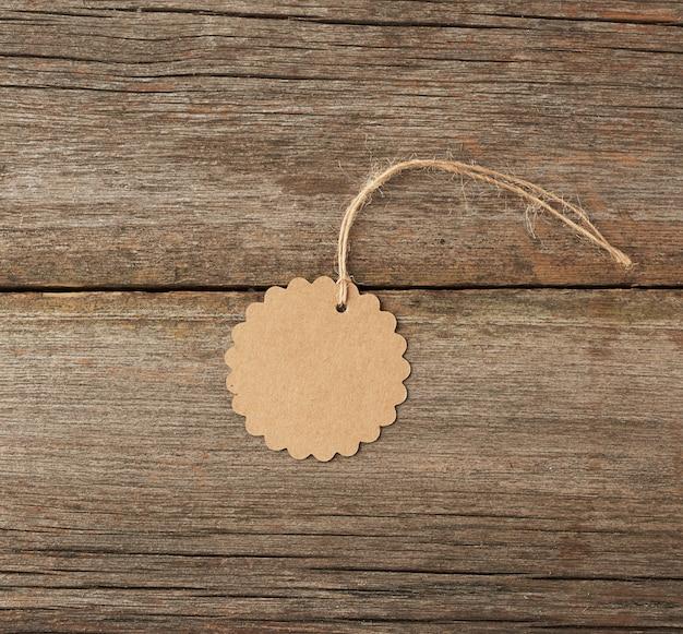 Okrągła pusta metka z brązowego papieru przewiązana białym sznurkiem