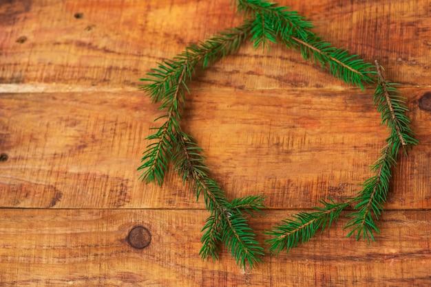 Okrągła rama gałęzi choinki na drewnianym tle. nowy rok, boże narodzenie w tle.