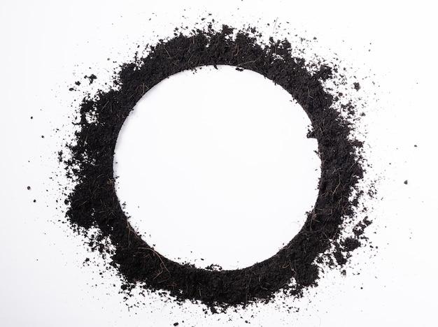 Okrągła rama okrągła czarnej ziemi na tle roślin
