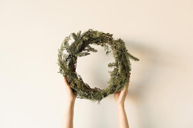 Okrągła rama wieniec wykonana z gałęzi jodły i eukaliptusa w damskich rękach na neutralnym tle.