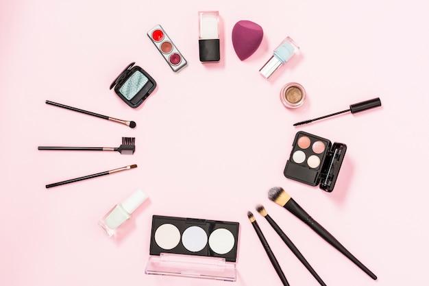 Okrągła rama wykonana z pędzlami do makijażu; butelka do paznokci; cień do powiek; blender na różowym tle