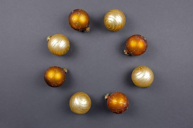 Okrągła rama wykonana ze złotych bombek na czarnym tle