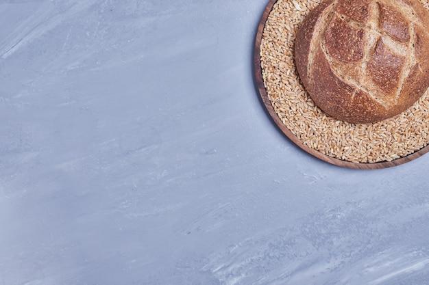 Okrągła, ręcznie robiona bułka na talerzu pszennym.