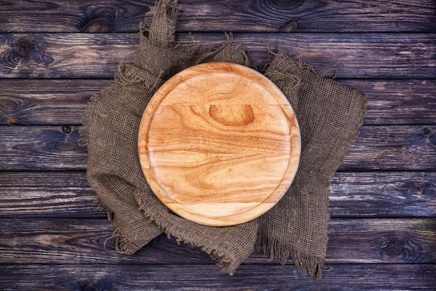 Okrągła taca do pizzy na ciemnym drewnianym stole.