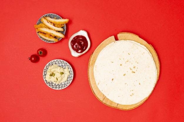 Okrągła tortilla z dipami obok smażonego kurczaka