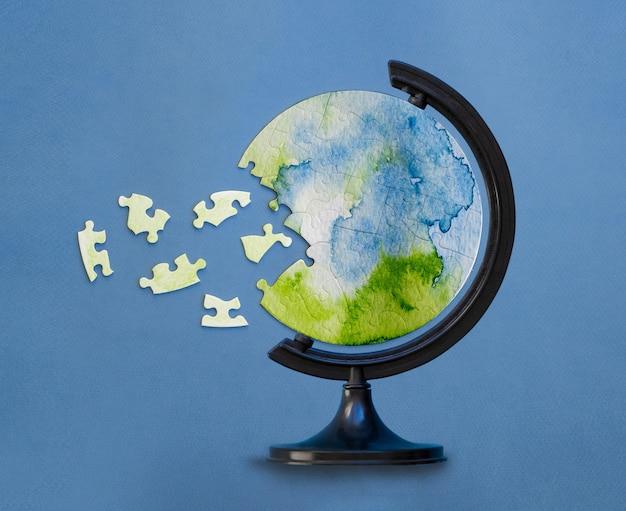 Okrągła układanka umieszczona w stojaku na świecie z niepołączonymi elementami. ochrona koncepcji planety