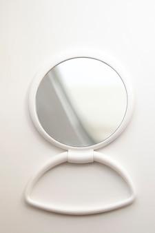 Okrągłe białe plastikowe lustro na białym plastikowym stojaku z odbiciem światła, odizolowane.