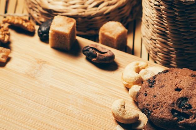 Okrągłe chrupiące czekoladowe ciasteczka z orzechami, chipsami kakaowymi i przyprawami na desce do krojenia z miejscem na kopię