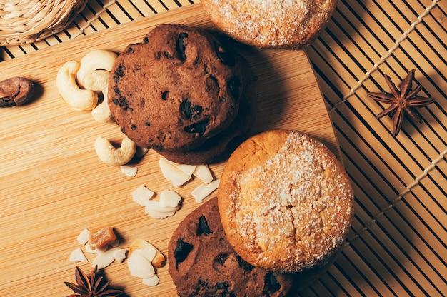 Okrągłe chrupiące czekoladowe ciasteczka z przyprawami i orzechami na desce do krojenia