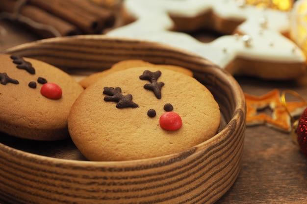 Okrągłe ciasteczka z twarzą jelenia bożego narodzenia z czerwonym nosem w drewnianym okrągłym talerzu na drewnianym stole.