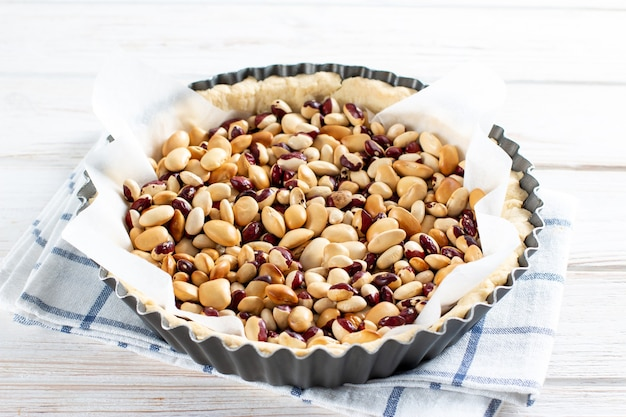 Okrągłe ciasto kruche z fasolą gotowe do pieczenia na ślepo. fasola używana jako masa do ciasta w surowym cieście wyłożonym papierem do pieczenia