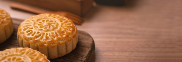 Okrągłe ciasto księżycowe mooncake - tradycyjne ciasto w stylu chińskim podczas mid-autumn festival / moon festival na drewnianym tle i tacy, z bliska