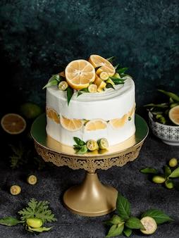 Okrągłe ciasto ozdobione białą śmietaną, cytryną i liśćmi mięty