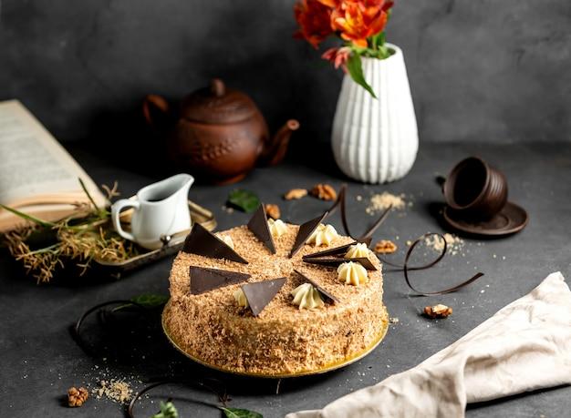 Okrągłe ciasto pokryte kruszonką zwieńczone kawałkami czekolady